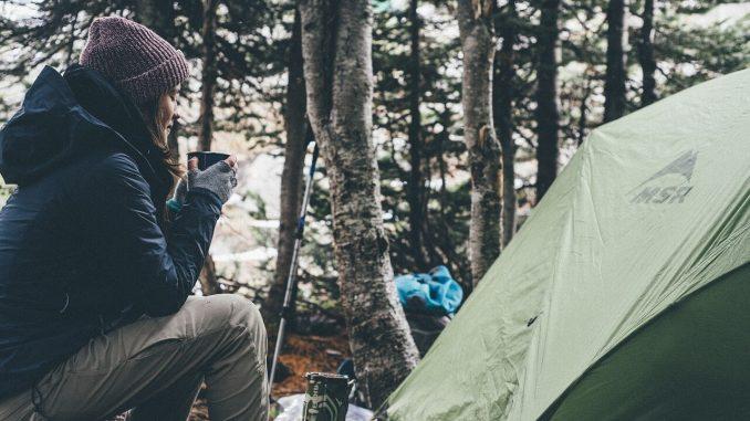 Frau mit Zelt im Wald